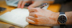 Image of man's hand holding a pen, writing in an open notebook.